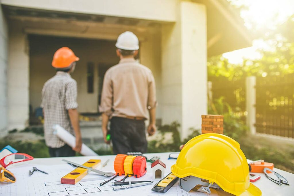 Two contractors looking at a house